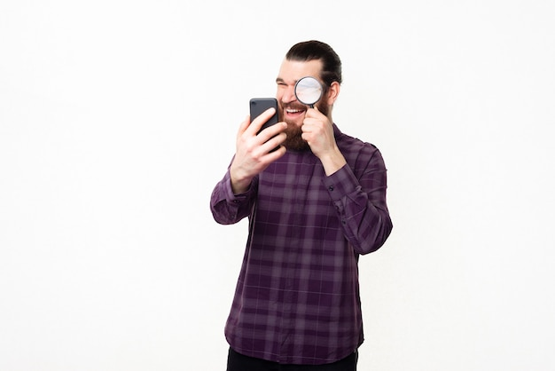 Photo of handsome man in checkered shirt looking trough magnifying glass at smartphone