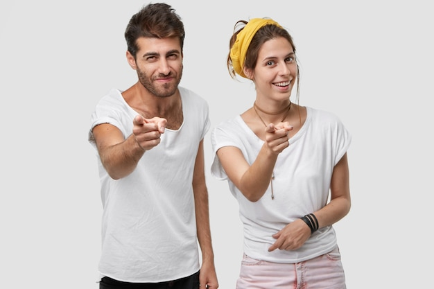 Photo of handsome man and european woman point  with both index fingers, make bang gesture, choose something