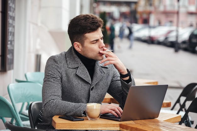 Photo of handsome man in gray coat smoking cigarette, and drinking cappuccino while resting in cafe outdoors