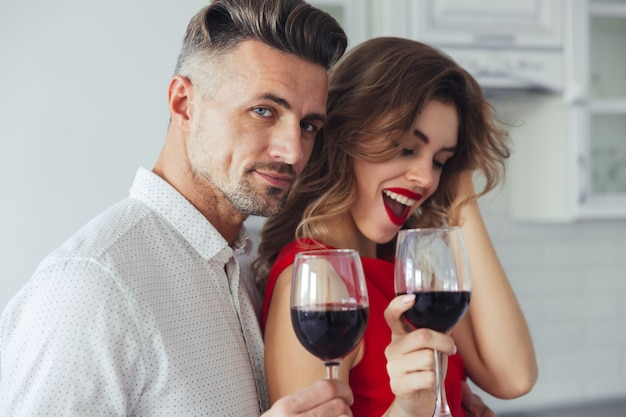 Photo of handsome man hug his woman while drinking wine