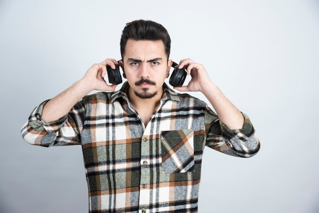 Photo of handsome man with headphones standing and looking over white wall.