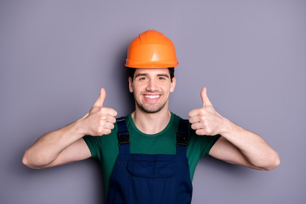 Photo of handsome masculine worker guy skilled engineer raise thumb fingers up advising good quality wear t-shirt blue safety dungarees protective helmet isolated grey wall