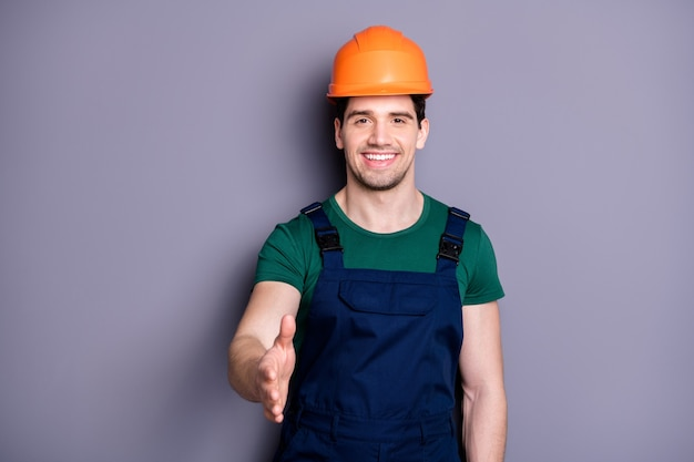 Photo of handsome masculine worker guy skilled engineer shaking arm boss customer making deal wear t-shirt blue safety dungarees protective helmet isolated grey wall