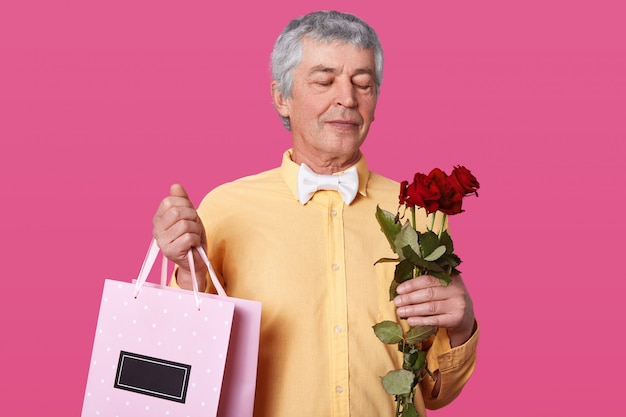 Photo of handsome mature man, wears elegant yellow shirt, bowtie, holds bouquet of red roses and pink bag with present for his wife