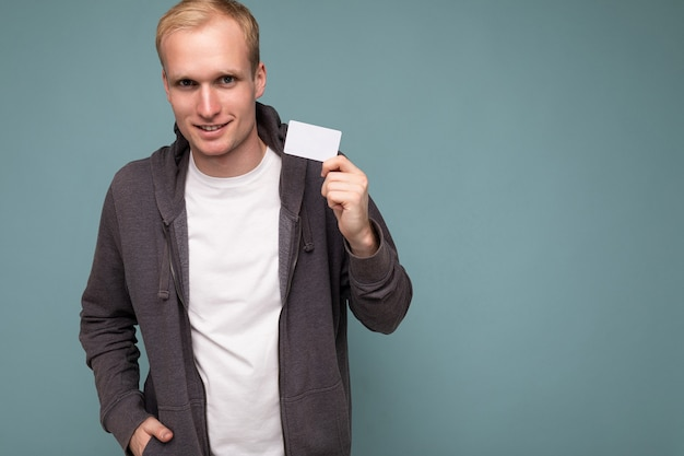 Photo of handsome positive blonde man wearing grey sweater and white t-shirt isolated over blue background wall holding credit card looking at camera. copy space