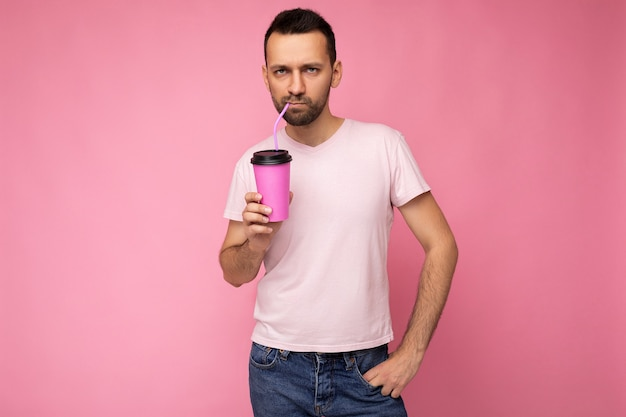 Photo of handsome positive young brunette unshaven man with beard wearing white t-shirt