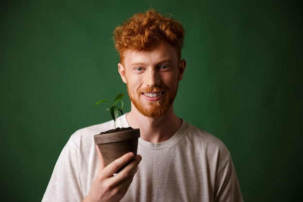 Photo of handsome redhead bearded young man, holding potted plant