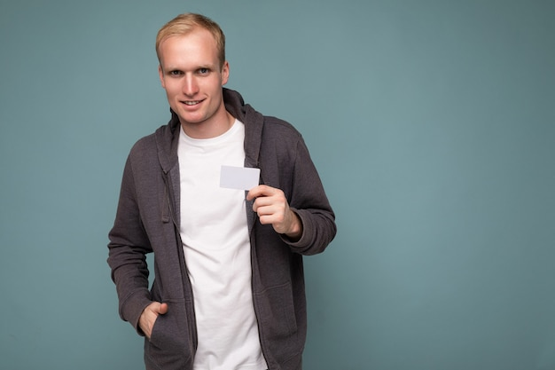 Photo of handsome selfconfident blonde man wearing grey sweater and white tshirt isolated over