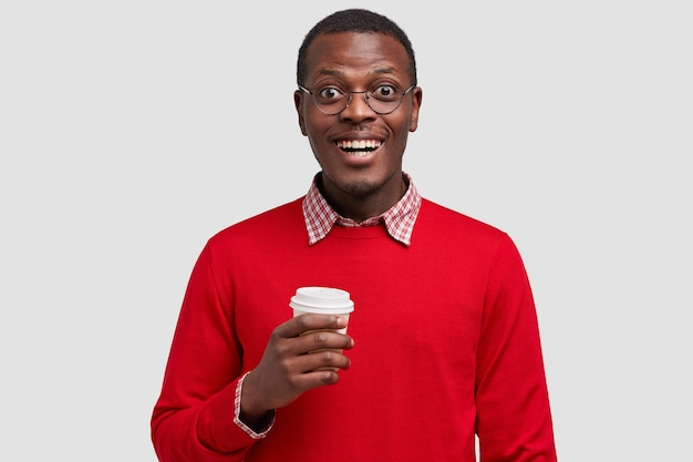 Photo of handsome smiling dark skinned young man dresssed in red jumper, holds takeaway coffee, being in good mood