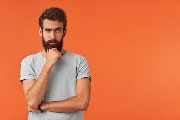 Photo of handsome young bearded man with brown eyes wearing white t-shirt casual style, standing right against red wall arm touch beard emotion skeptic doubter cynic