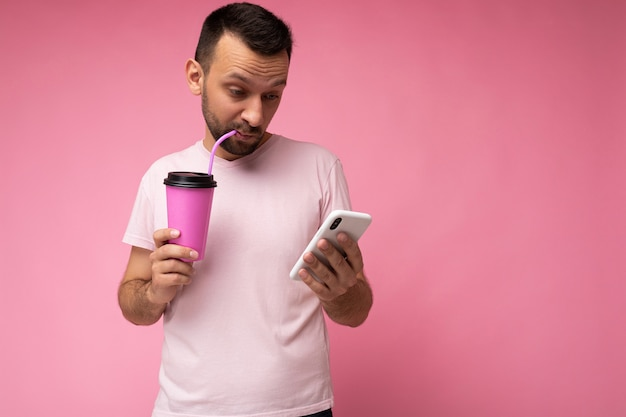 Photo of handsome young unshaven brunette man with beard wearing everyday light pink t-shirt