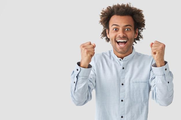 Foto di felice ragazzo afroamericano con espressione positiva, stringe i pugni con felicità, esulta per il suo successo, vestito con abiti eleganti, posa contro il muro bianco, copia spazio da parte