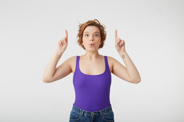 Photo of happy amazed young attractive short-haired girl, opened her mouth in surprise, pointing up at the copy space, stands over white wall.