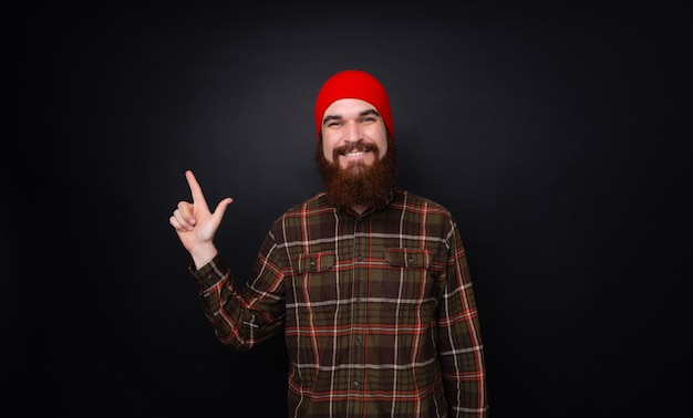 Photo of happy bearded man over dark wall pointing up with finger