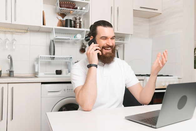 Photo of happy bearded man talking on phone sitting near laptop in kitchen , working from home