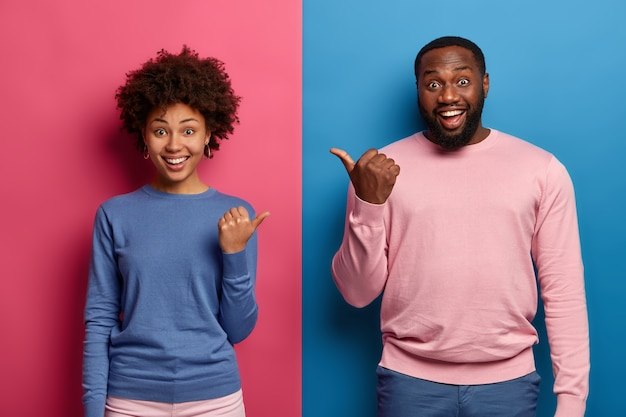 Photo of happy black woman and man spouse point thumbs at each other, have good mood, suggests to choose one of them, smile happily