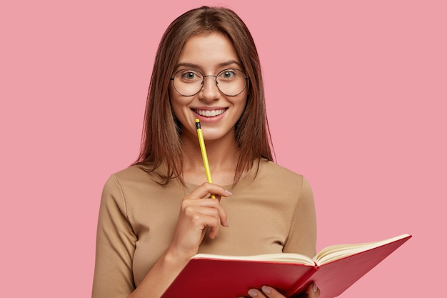 Photo of happy brunette woman with positive smile, carries textbook, holds pencil for writing