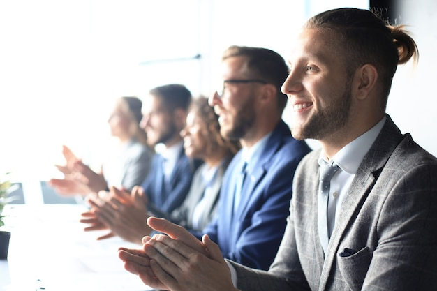 Photo of happy business people applauding at conference.