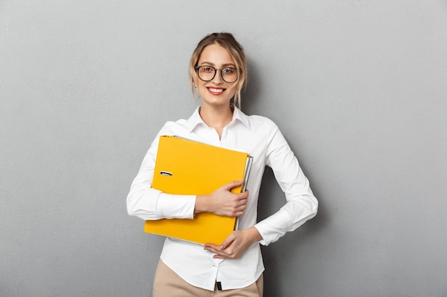 Photo of happy businesswoman wearing glasses holding paper folders in the office, isolated