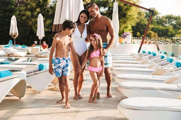 Photo of happy caucasian family with children resting near luxury swimming pool with white fashion deckchairs and umbrellas, outdoor during recreation