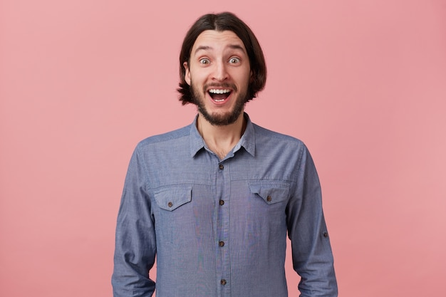 Photo of happy cheerful amazed bearded young man with long combed dark hair in denim shirt, heard the good news, was delighted, with open mouth, isolated over pink background.