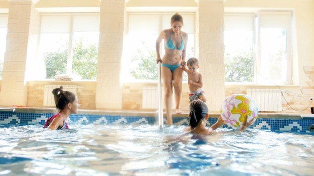 Photo of happy cheerful family having fun in swimming pool. young mother with three children in gym with swimming pool