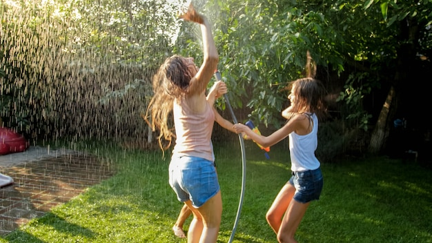 Photo of happy cheerful girls in wet clothes dancing and jumping under water garden hose. family playing and having fun outdoors at summer