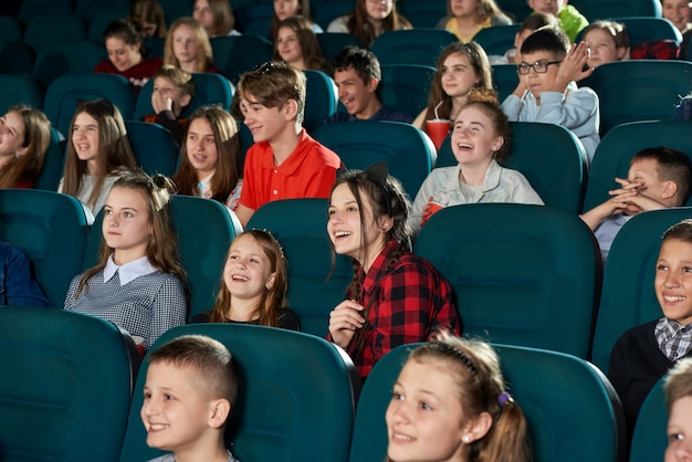 Photo of happy children watching movie in the cinema and laughing.