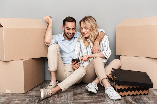 Photo of happy couple in casual clothing seating near cardboard boxes and looking at smartphone isolated over gray wall