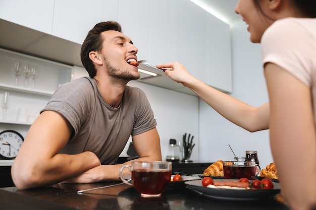 Photo of happy couple man and woman sitting at table in flat, and having breakfast together
