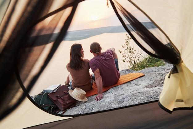 Photo of happy couple sitting in tent with a view of lake during hiking trip.