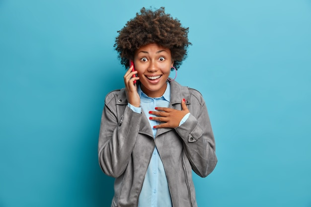 Photo of happy curly haired teenage girl surprised cheerful expression talks via mobile phone reacts surprisingly on awesome news wears grey jacket
