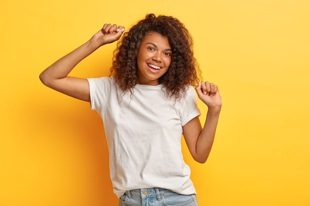 Photo of happy dark haired woman with positive expression, raises arms and moves while dancing, dressed in white casual t shirt and jeans