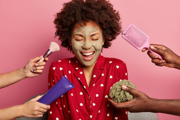 Photo of happy dark skinned young woman applies purifying clay mask, wears red pajama, has eyes closed, gets cosmetic treatments