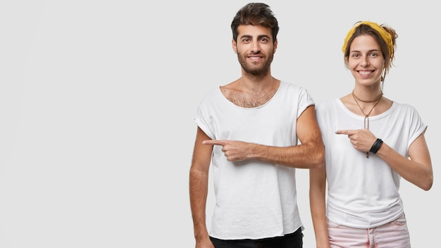 Photo of happy delighted woman and man dressed casualy, point at right side, show free space for your promotion or advertisement