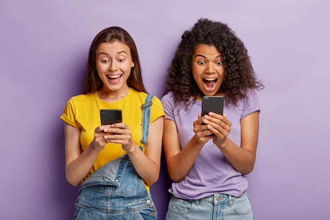 Photo of happy diverse female friends ignore live communication, chat in web blog via cell phones, gaze with positive expressions at screens