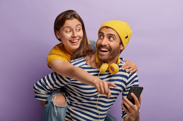 Photo of happy european couple have fun together, use modern technologies for entertainment. glad man gives piggyback to girlfriend, wears yellow hat and striped jumper, holds cellular, shows pictures