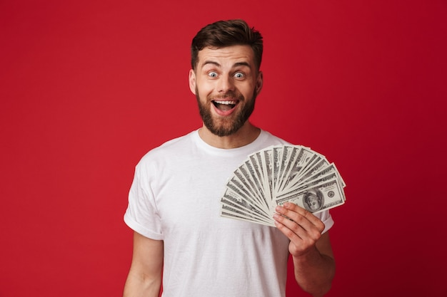 Photo of happy european man in casual t-shirt smiling and holding fan of money in dollar banknotes, isolated over red wall
