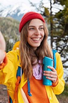 La foto di una donna europea felice ha un ampio sorriso, mostra denti bianchi e perfetti, fa una foto di se stessa, fa una pausa caffè