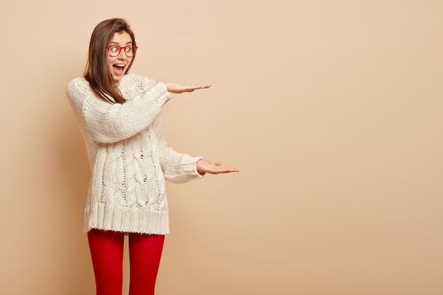 La foto di una donna eccitata felice fa un grande gesto con entrambe le mani, colpita dalle enormi dimensioni della confezione regalo ricevuta