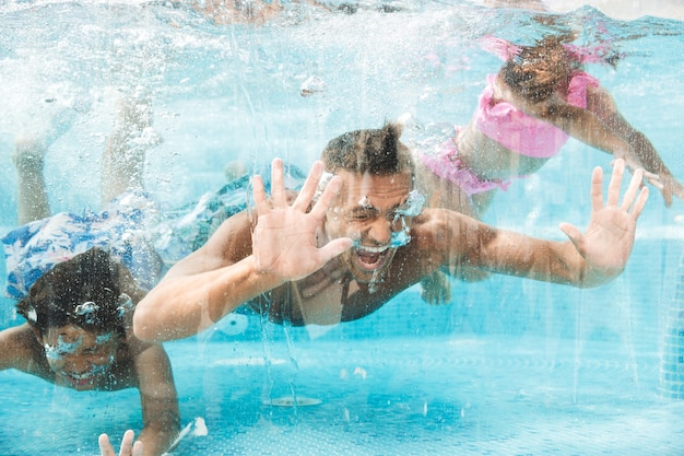 Photo of happy family father with children diving and swimming under water in pool, during summer vacation