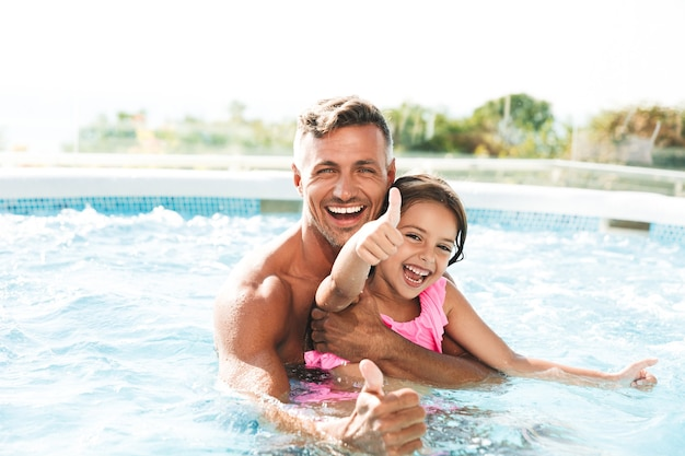 Photo of happy family father with daughter smiling, while swimming in pool outdoor during summer vacation