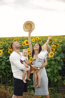 Photo of happy family. parents and daughter. family together in sunflower field. man in a white shirt.