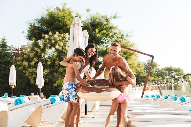 Photo of happy family with kids resting near luxury swimming pool, and having fun with rubber ring outside hotel