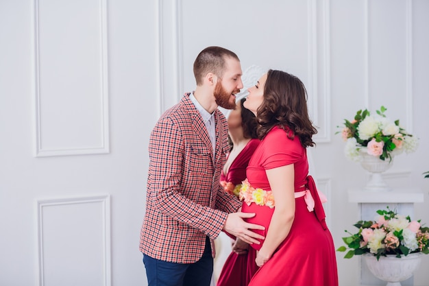 Photo of happy future father look at his pregnant wife. husband and pregnant on a mirror background.