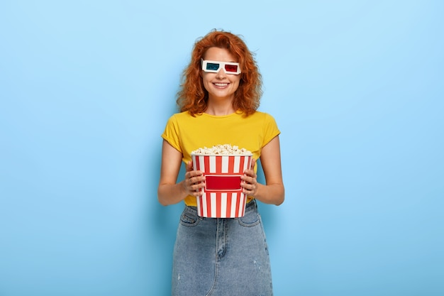 Photo of happy ginger charming girl holds bucket with popcorn