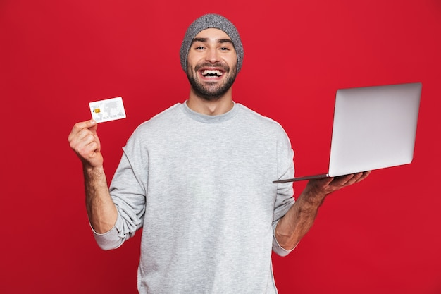 Photo of happy guy 30s in casual wear holding credit card and silver laptop isolated