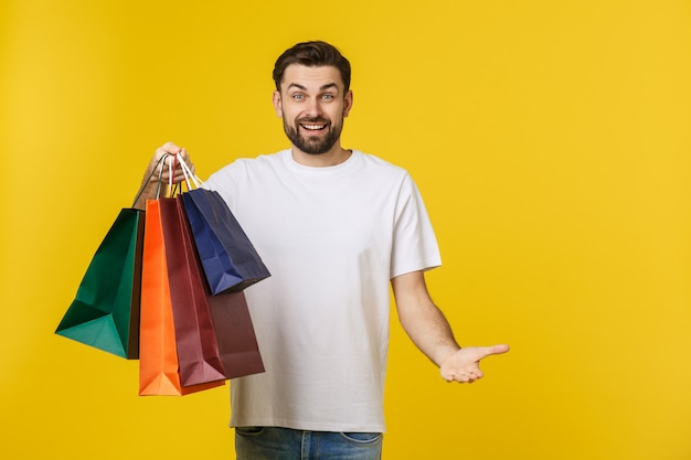 Photo of happy guy, holding shopping bags, isolated over yellow