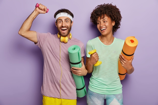 Photo of happy guy and woman work on biceps with weights, carry karemats, have joyful expressions, enjoy training together, dressed in casual wear, being motivated for healthy lifestyle and sport