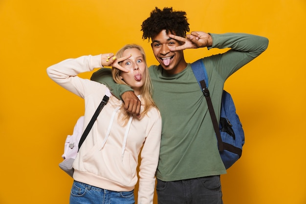 Photo of happy hipsters guy and girl 16-18 wearing backpacks laughing at camera, isolated over yellow background